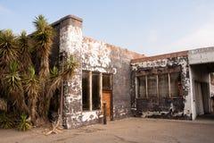 Palmiers près de ville fantôme abandonnée de station service de gaz images stock