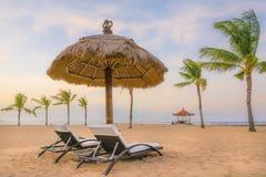 Palmiers sur la plage sablonneuse, le lit pliant deux et le parasol blancs Vue de plage tropicale gentille Image libre de droits