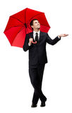 Palming up man with red umbrella checks the rain. Palming up man with opened umbrella checks the rain, isolated on white Stock Photography