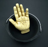 Palmistry hand in cauldron. Palmistry hand sculpture sits inside of a black cast iron cauldron Royalty Free Stock Photography