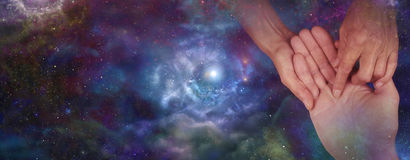 Palmistry website header on night sky. Palmist holding man's hand and inspecting the lines with an outer space night sky background banner Royalty Free Stock Photography