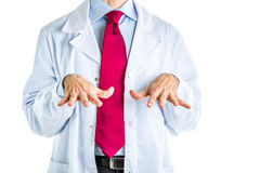Palms down gesture by doctor in white coat. Caucasian male doctor dressed in white coat, blue shirt and red tie is making palms down gesture to point out Royalty Free Stock Photography