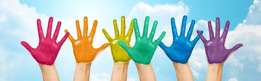 Palms of human hands painted in rainbow colors. People, gay pride, creativity and art concept - palms of human hands painted in rainbow colors over blue sky and royalty free stock photo