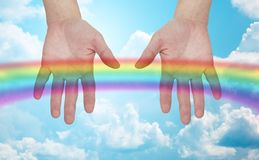 Palms of human hands thumbs up over rainbow in sky Stock Photo