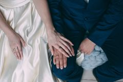 Palms of the newly-married couple with wedding rings.  Stock Images