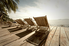 Palms and relaxing sunbeds Royalty Free Stock Photography