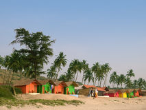 Palms and small guest houses on a beach. Line of colour huts at the sea coast Stock Images
