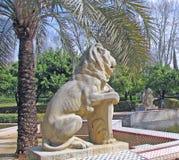 Palmträd och skulpturer av lejonet i parkera Fotografering för Bildbyråer