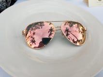 Palmträd reflekterade i rosa solglasögon på den vita plattan arkivfoton