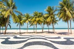 Palmträd och den iconic Copacabanaen sätter på land mosaiktrottoaren Royaltyfri Fotografi