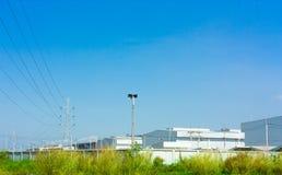 Palo ad alta tensione alla fabbrica con verde Immagini Stock Libere da Diritti