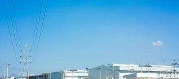 Palo ad alta tensione allo spazio del cielo della fabbrica Fotografia Stock