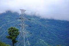 Palo ad alta tensione del primo piano sulla montagna verde fotografia stock libera da diritti