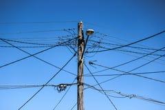 Palo ad alta tensione di elettricità con collegamenti, la lampada di via ed il cielo blu complessi Fotografia Stock