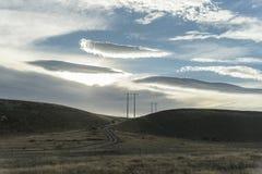 Palo ad alta tensione di elettricità nella collina Immagine Stock