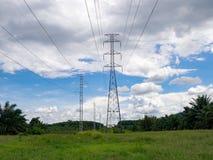 Palo ad alta tensione di energia elettrica nel campo verde contro con la nuvola di bianco del cielo blu Fotografia Stock Libera da Diritti