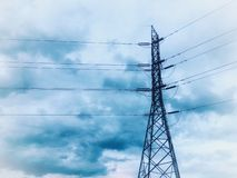 Palo ad alta tensione di energia elettrica sotto la nuvola blu immagini stock