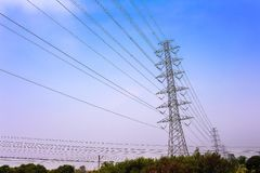 Palo ad alta tensione su cielo blu con le nuvole fondo e paesaggio di rurale fotografie stock