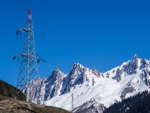 Palo ad alta tensione sulla cima della montagna con il fondo della neve fotografia stock libera da diritti