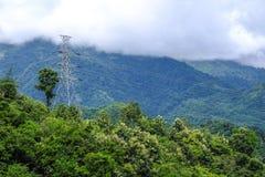 Palo ad alta tensione sulla montagna e sulla nebbia verdi immagini stock