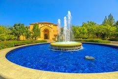 Stanford Auditorium and Fountain. Palo Alto, CA, United States - August 13, 2018: Fountain and Memorial Auditorium on background. Stanford University is one of stock image
