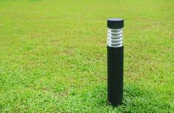 Palo alto vicino della lampada nel campo di erba verde immagine stock libera da diritti