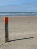 Palo con il numero 63 sulla spiaggia Fotografia Stock