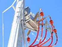 palo d'acciaio con il trasformatore elettrico ed elettrico ad alta tensione rosso Fotografia Stock Libera da Diritti