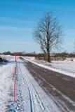 Palo della neve da un lato della strada campestre Fotografia Stock Libera da Diritti