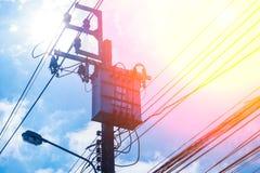 Palo di elettricità del trasformatore e linea elettrica ad alta tensione con il fondo blu del cielo nuvoloso Immagini Stock Libere da Diritti
