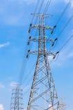 Palo di potere e linea di elettricità ad alta tensione con il backg del cielo blu Immagine Stock