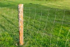Palo e recinto di filo metallico di legno, con il prato verde nel fondo lontano fotografie stock libere da diritti