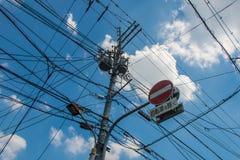 Palo eléctrico y del teléfono sucio caótico en Kyoto imagen de archivo