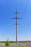 Palo elettrico ad alta tensione con i cavi su un fondo della SK blu Fotografie Stock Libere da Diritti