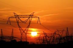 Palo elettrico ad alta tensione durante il tramonto Fotografie Stock Libere da Diritti