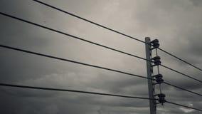 Palo elettrico che sta con il cavo elettrico ed il fondo in bianco e nero della nuvola Fotografie Stock