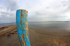 Palo per l'attracco delle navi sulla spiaggia del mare Immagini Stock Libere da Diritti