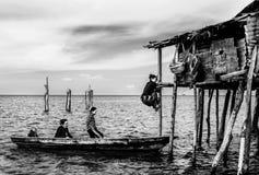 Palo rampicante di signora tribale per entrare nella sua casa e nella sua famiglia che aspettano il loro giro, Sabah Semporna, Ma fotografia stock libera da diritti