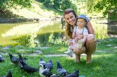 Palomas de alimentación de la mamá y de la hija en un parque en el lago Imagenes de archivo