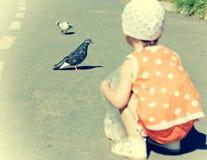 Palomas de alimentación de la niña. Fotografía de archivo libre de regalías