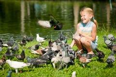 Palomas de alimentación de la niña en el parque Fotos de archivo libres de regalías