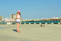 Palomas de alimentación de la niña en la costa Imágenes de archivo libres de regalías