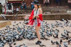 Palomas de alimentación de la muchacha turística hermosa en Katmandu Durbar Squar fotografía de archivo