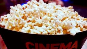 Palomitas de maíz en caja del cartón con la palabra del cine escrita en ella almacen de video