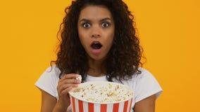 Palomitas de maíz femenina bonita joven de la consumición, película emocionante de observación en cine, afición metrajes