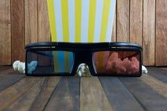 Palomitas de maíz y vidrios 3d en el fondo de madera Fotografía de archivo libre de regalías