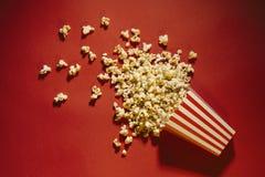 Palomitas derramadas en un fondo, un cine, películas y un entertai rojos imagenes de archivo