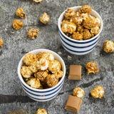Palomitas dulces del caramelo en dos cuencos azules rayados blancos de cerámica en un fondo de piedra gris elegante Foco selectiv Fotos de archivo