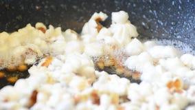 Palomitas en aceite caliente en un primer de la cacerola del Teflon
