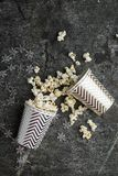 Palomitas en las tazas grises de papel de la Navidad blanca para las reuniones de las vacaciones de invierno con los amigos con l Imágenes de archivo libres de regalías